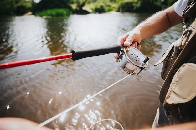 湖や川で釣りをする若い漁師。男の手でロッドのカットビュー。プロの川の趣味。ロッドを使って魚を捕まえる。ビューをカットします。晴れた日。