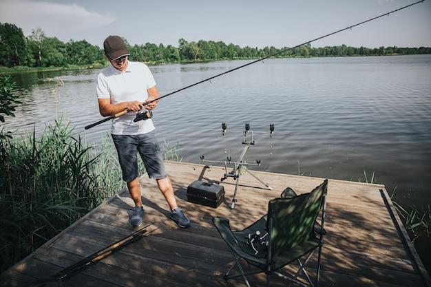 호수 또는 강에서 낚시하는 젊은 어 부. 낚시 릴을 사용하고 조정하여 낚시를 준비합니다. 긴 막대를 잡고 강가에 홀로 서십시오.