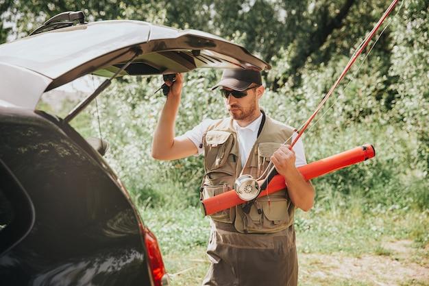 Молодой рыбак рыбалка на озере или реке. парень держит багажник машины открытым и собирается закрыть его перед рыбалкой. готовим оборудование. собираемся в одиночку порыбачить на реке или озере.