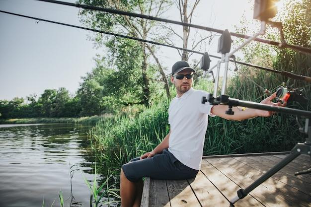 Молодой рыбак рыбалка на озере или реке. парень сидит один у водной пристани и оглядывается на удочки. отрегулируйте их для водной охоты. рыбак держит ноги в воде.