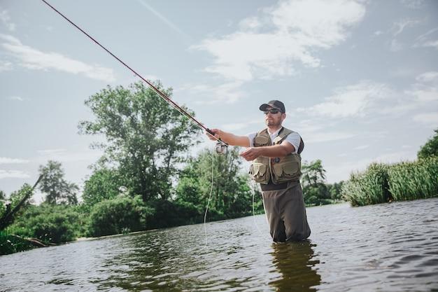 湖や川で釣りをする若い漁師。長い棒を持って魚を捕まえるためにそれを使用しているロブの男の低いビュー。一人で川や湖の水に立ってください。魚の狩猟。活動中のプロの漁師。