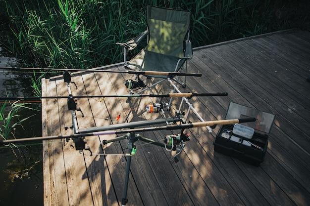 湖や川で釣りをする若い漁師。川や湖の岸にある釣り竿の写真。人のいない空の場所。釣りのための完全な機器。晴れた日。