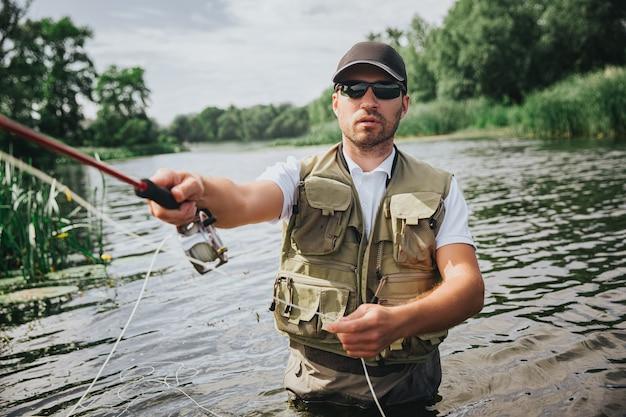 湖や川で釣りをする若い漁師。ロッドを手に持ってアクティブフィッシングをしている男性の写真。川や湖の真ん中で一人で立ってください。真面目な集中男釣り。