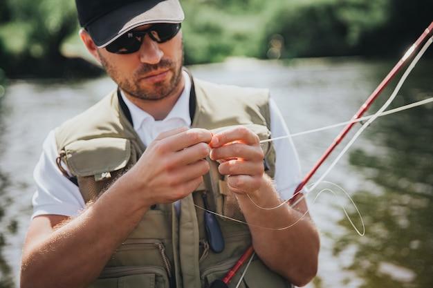 湖や川で釣りをする若い漁師。美味しい魚を釣るために水に入れる前に、釣り糸にルアーを使用するプロセスの写真。写真の深刻な残忍な漁師。