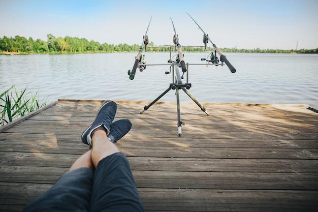 Молодой рыбак рыбалка на озере или реке. фотография расслабленного парня, сидящего в одиночестве на пирсе и смотрящего на три удочки. хобби, время и процесс водной охоты. взгляд рыбака глазами.