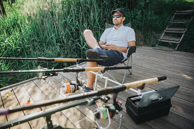 Молодой рыбак рыбалка на озере или реке. расслабленное сидение в складном кресле перед тремя удочками для рыбалки. профессиональное рыболовное снаряжение. сидя на берегу озера или реки.