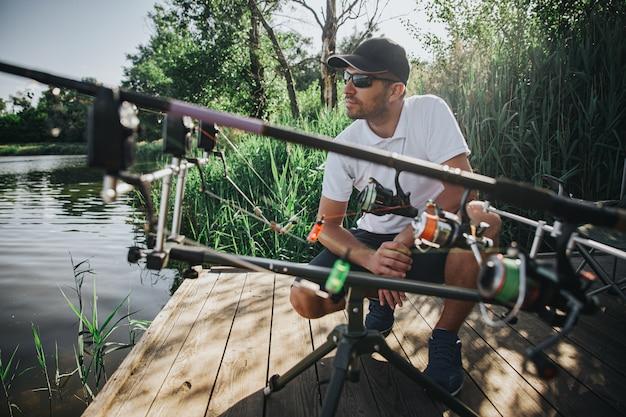 Молодой рыбак рыбалка на озере или реке. серьезный сконцентрированный профессиональный взрослый парень, сидящий на корточках у удочек и смотрящий на воду. жду новой свежей рыбы.