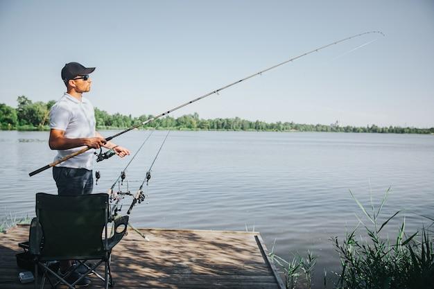 Молодой рыбак рыбалка на озере или реке. вид сбоку взрослого парня, ловящего рыбу на реке или озере. мужчина держит стержень в руках. солнечный прекрасный день для получения свежей вкусной рыбы.
