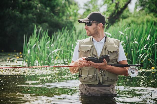 湖や川で釣りをする若い漁師。ロッドといくつかの釣り道具を持っている深刻な忙しい人の側面図。水中で一人で立ちます。ボックス内のプラスチックルアー。