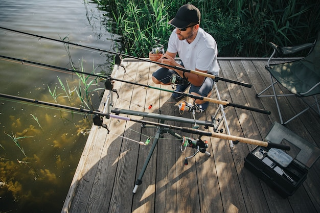 湖や川で釣りをする若い漁師。釣りの過程でロッドを調整する男のアップビュー。新しい新鮮なおいしい魚を待っています。日光と晴れた日。