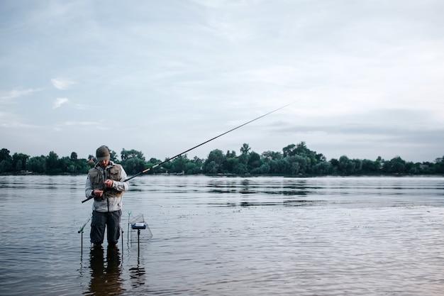 Молодой рыбак стоит босиком в воде и держит муху. он смотрит на это. парень работает с ложкой и приманкой. он стоит возле крючков, которые одним концом кладут в воду.