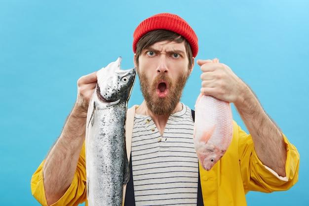 カメラに2匹の魚を示す若い漁師