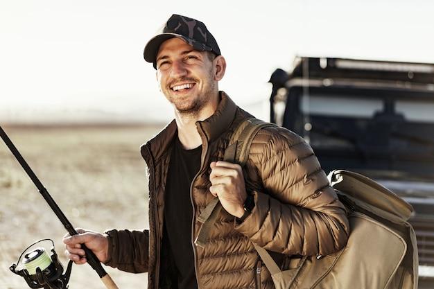 그의 차 근처에 서서 낚시 장비를 들고 있는 젊은 어부
