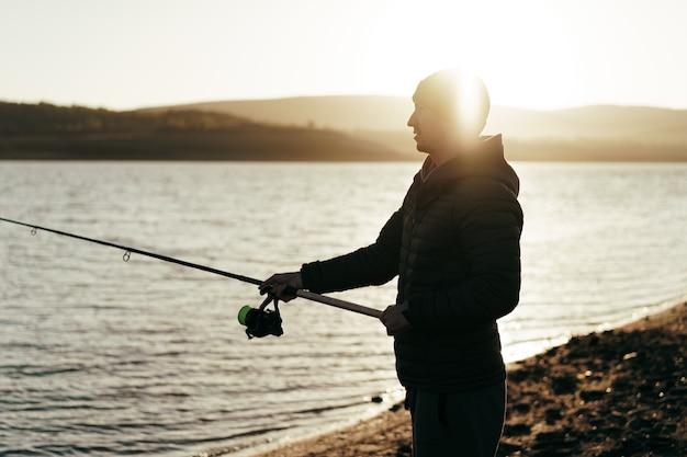 釣り竿と湖の岸に立っている若い漁師
