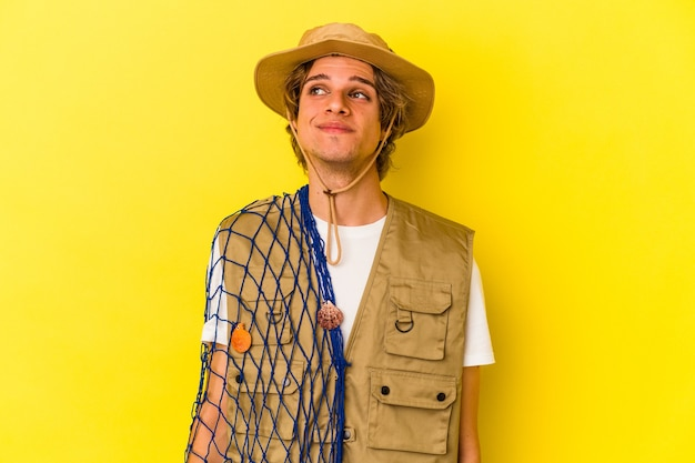 Young fisherman with makeup holding a net isolated on yellow background  dreaming of achieving goals and purposes