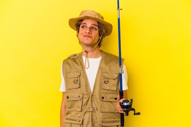目標と目的を達成することを夢見ている黄色の背景に分離された化粧保持棒を持つ若い漁師