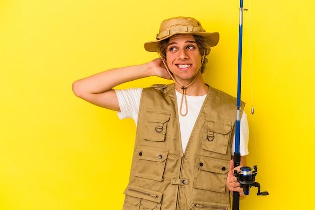 노란색 배경에 격리된 화장대를 들고 머리를 만지고 생각하고 선택하는 젊은 어부.