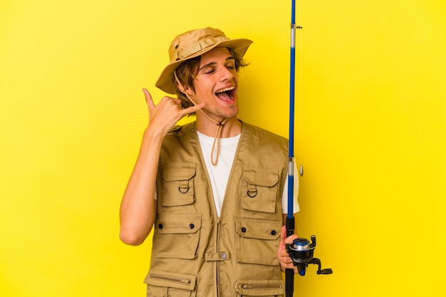 Young fisherman with makeup holding rod isolated on yellow background  showing a mobile phone call gesture with fingers.