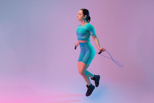 Молодая подтянутая и спортивная женщина прыгает через скакалку на градиентном фоне. подходит спортсменка позирует, уверенно выглядит. идеальное тело, готовое к лету. красота, курорт, спортивная концепция. листовка.