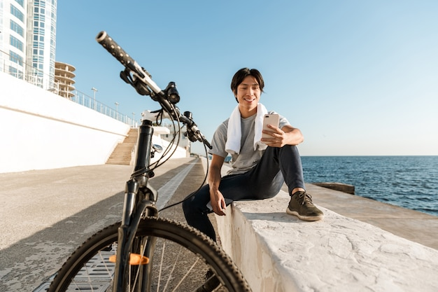 Young fit asian man bicyclist working out oudoors, sitting at the seaside
