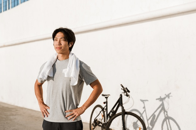 Young fit asian man bicyclist working out oudoors, standing