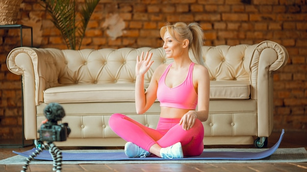 Young fit blogger girl seating on yoga mat in sport outfit with camera doing online workout at home, exercise on camera