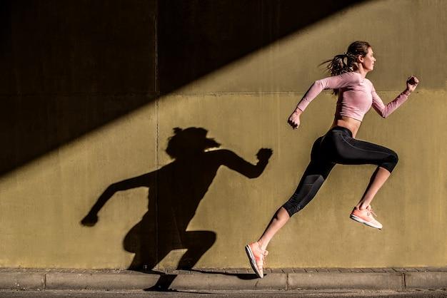 若いフィット通りでジャンプ金髪の女性