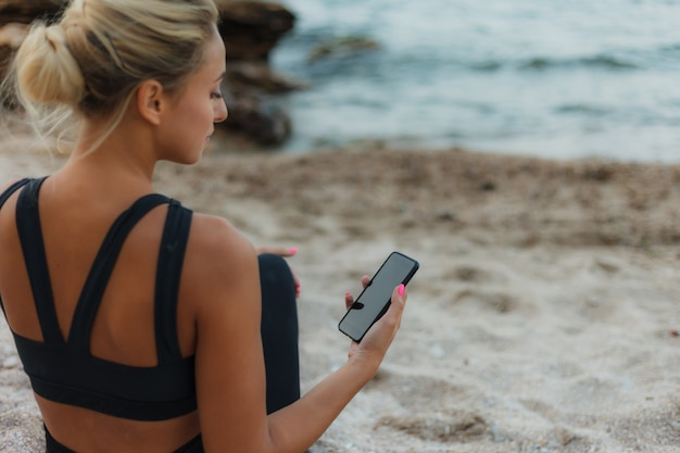 Young fit blonde woman in sportswear sits on the sand at wild beach and holds smartphone in her hand.