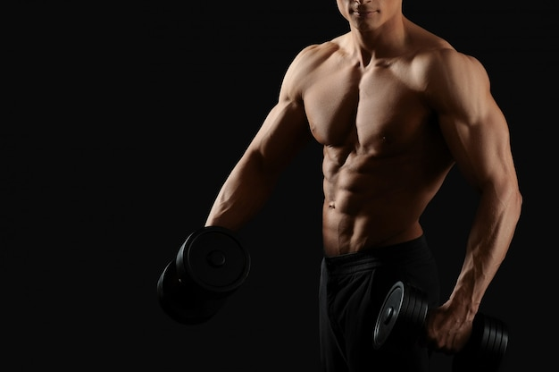 Молодой культурист, тренирующийся с гантелями, позирует без рубашки на черном
