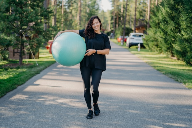 Young fit brunette woman holds big fitness ball, dressed in active wear, does exercises workout, poses in park, walks outdoor and breathes fresh air. people, gymnastics and aerobics concept.