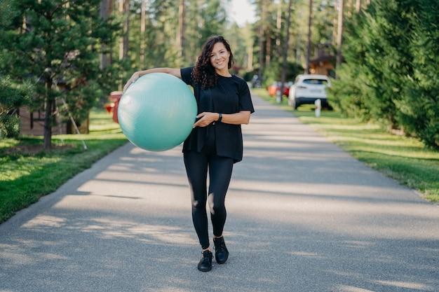 若いフィットブルネットの女性は、アクティブな服を着て、大きなフィットネスボールを保持し、運動トレーニングを行い、公園でポーズをとり、屋外を歩き、新鮮な空気を吸います。人、体操、エアロビクスのコンセプト。