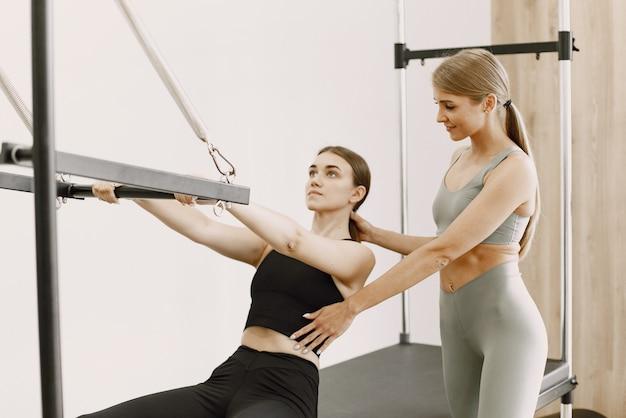 Giovane donna bruna in forma con un allenatore femminile biondo in palestra. donna che indossa abbigliamento sportivo nero. ragazza caucasica che allunga con l'attrezzatura.