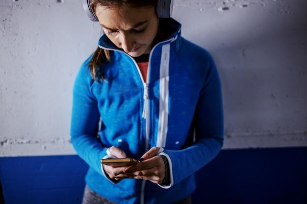 Молодая подходящая кавказская спортсменка в спортивном костюме быстро работает в гараже.