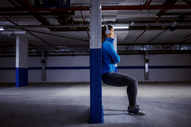 Young fit caucasian sportswoman in tracksuit running fast in garage.