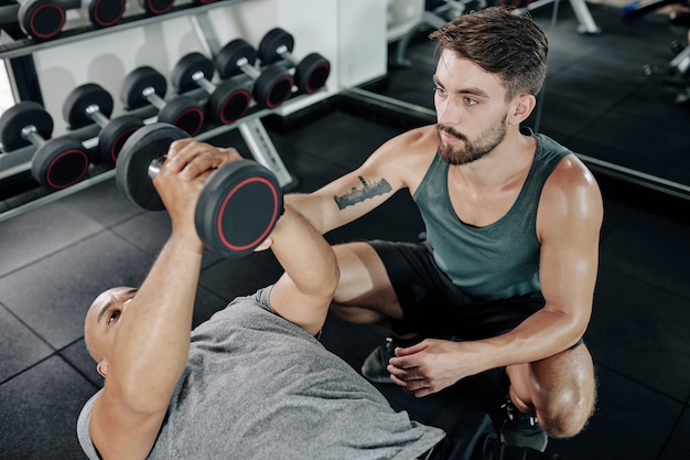 Молодой фитнес-тренер контролирует зрелого клиента, выполняющего разгибание одной гантели лежа и пытающегося сосредоточиться на работе трицепса