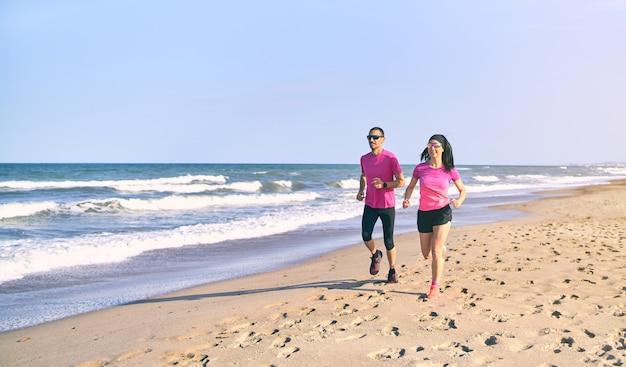젊은 맞는 일출 동안 해변에서 실행하는 커플. 건강한 하루의 시작. 분홍색과 검은 색 운동복을 입고 있습니다. 바다로 달리기.