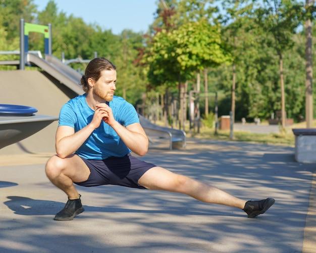 Молодой подтянутый европейец в спортивной одежде растягивает ноги во время разминки