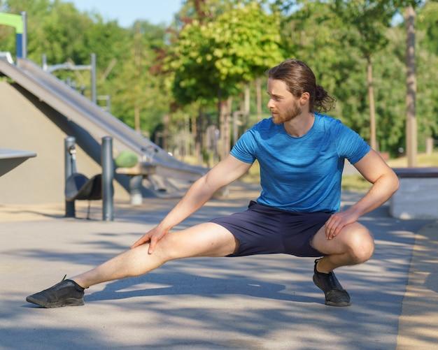 Молодой подтянутый европейский мужчина в спортивной одежде растягивает ноги во время разминки на открытом воздухе