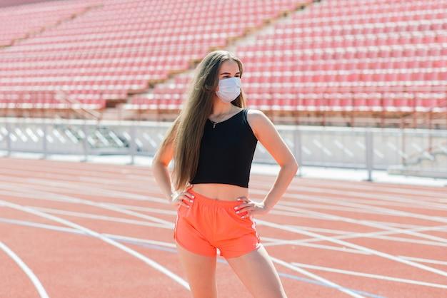 Молодая женщина в спортивной одежде и защитной маске от коронавируса на красной дорожке и волейбольной площадке во время тренировки на открытом воздухе на стадионе
