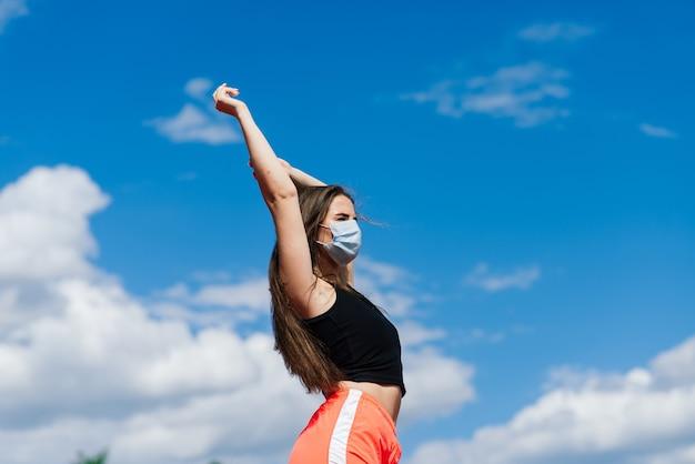 빨간색 트랙과 배구장에서 코로나 바이러스에 대한 스포츠웨어 및 보호 마스크를 입은 젊은 여성