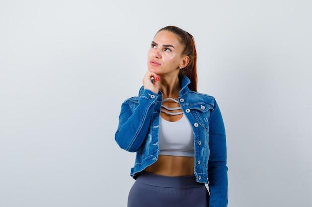 トップに若いフィットの女性、思考ポーズで立って混乱しているように見えるデニムジャケット、正面図。