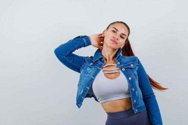 Young fit female keeping hand behind neck in top, denim jacket and looking cheerless. front view.