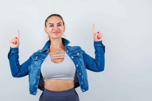 Young fit female pointing up in top, denim jacket and looking cheerful. front view.