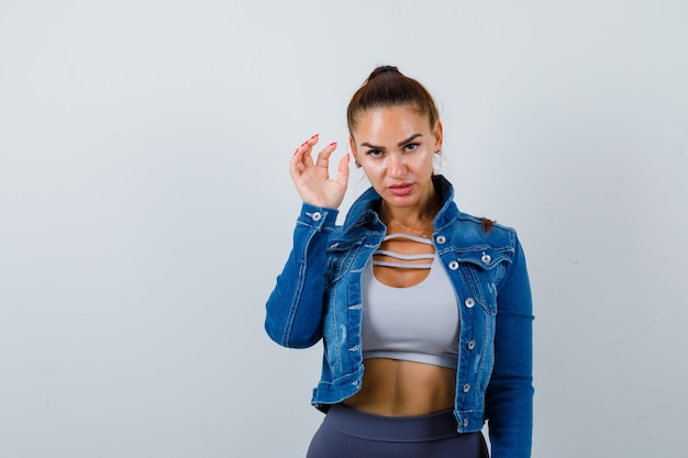 Young fit female in top, denim jacket showing claw imitating cat and looking aggressive , front view.