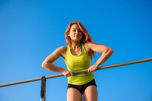 若いフィットの女性のトレーニングは、空のfackgroundで屋外でエクササイズを行います。