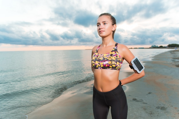 Young fit girl doing morning exercises on beach at sunrise