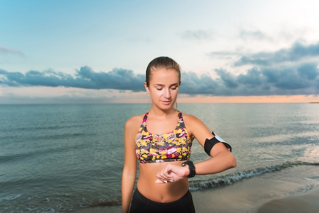 Young fit girl looking at watch during morning exercises on beach sunrise