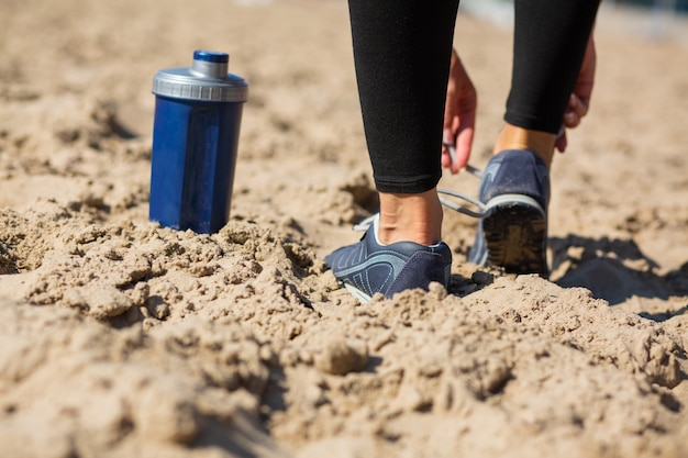 ビーチで靴紐を結ぶ若いフィットの女の子。テキスト用のスペース