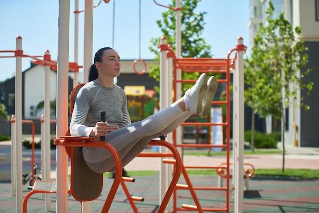 운동장에서 운동하는 젊은 맞는 소녀는 고르지 않은 막대에 다리를 올리면서 언론을 흔 듭니다. 측면보기.