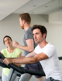 Young fit happy people cardio workout at gym